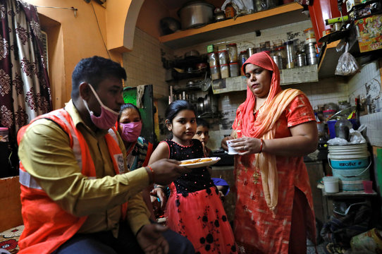 Dev Dutt Sharma, a sanitation worker, holds a plate with biscuits as his wife offers him tea before he leaves for work, during an extended nationwide lockdown to slow the spread of the coronavirus disease (COVID-19), in New Delhi