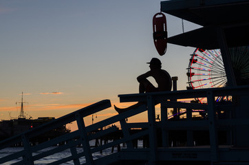 Silhouette Man Sitting At Santa Monica Pier Against Sky During Sunset