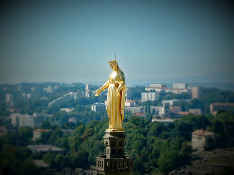 Statue Of Virgin Mary And City Against Blue Sky