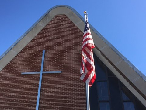 Low Angle View Of American Flag Against Church