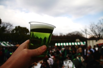 Cropped Image Of Person Holding Beer Glass Against Sky During St Patrick Day
