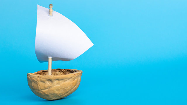 a small boat made of nutshell with a white sail on the blue background. Journey banner template.