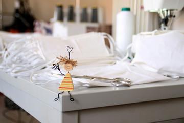 Gruß aus der Schneiderei von der Tischkante. Mit Lächeln und Herz werden Mundmasken hergestellt. Hilfe gegen Corona Virus Pandämie in der Welt