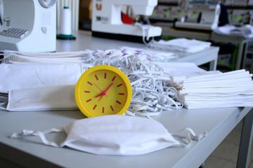 Zeit spielt große Rolle im Zeitraum der Pandämie. .Herstellung von Mundschutzmasken aus Baumwollstoff in einer Manufaktur um die Gesundheit vor einer Infektion mit dem Coronavirus zu schützen