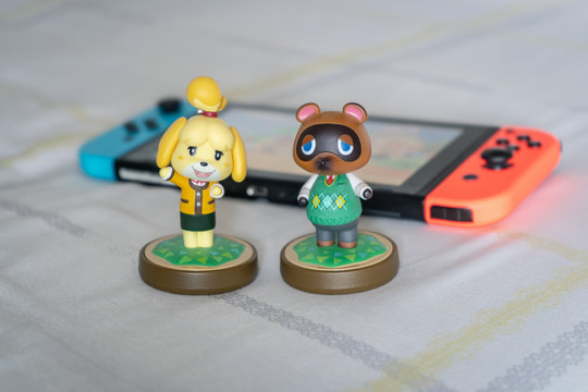 Bangkok, Thailand - March 21, 2020 : Amiibo presents Isabelle and Tom Nook, the characters from Animal Crossing game. Amiibo, an action figure, can interact with the Nintendo Switch game console.