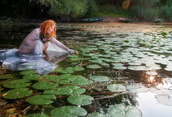 Young sexy woman Redhead with curly red hair sits joyfully, smiling, with white dress happy in the water in the lake