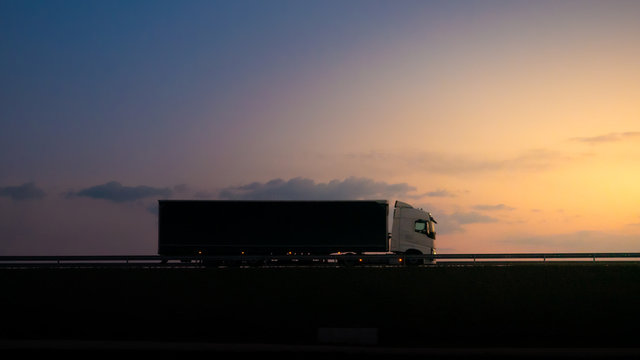 Silhouette of a truck on road at sunset.Semi truck trailer silhouette with setting sun.Delivery truck on asphalt road highway at sunset.Truck passing by a railing. Underexposed pic.