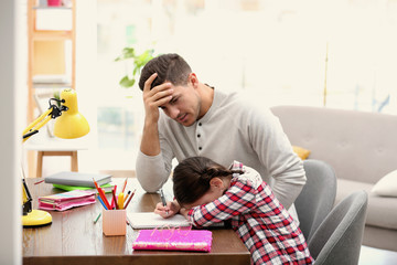 Upset father and daughter doing homework together at table indoors