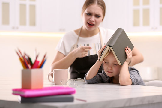 Mother scolding her daughter while helping with homework in kitchen