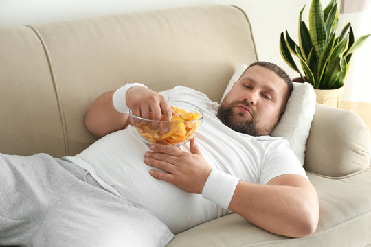 Lazy overweight man eating chips on sofa at home