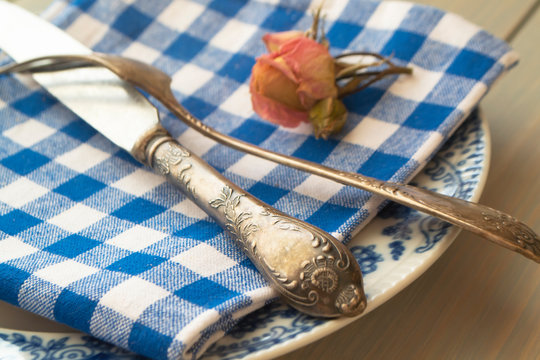 Vintage blue and white dinner plates, ornate vintage silver cutlery with pink rose