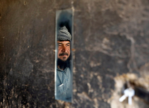 A man is reflected in a mirror as he looks at police officers near the shops during the coronavirus disease (COVID-19) outbreak in Kabul