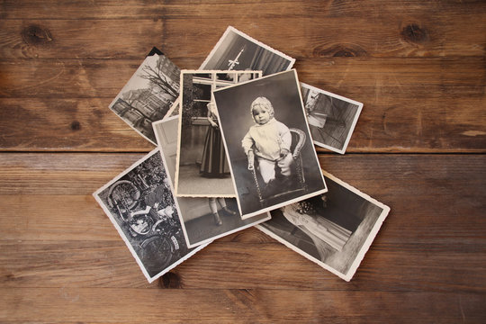 old vintage monochrome photographs in sepia color are scattered on a wooden table, the concept of genealogy, the memory of ancestors, family ties, memories of childhood
