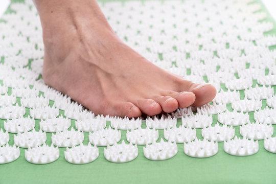 Female foot on an acupuncture rug. Acupuncture, massage. Alternative medicine.