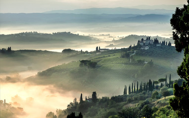 Sunrise over misty landscape of Italy. Early morning over rural area with gardens, farms, trees, fields in Tuscany province