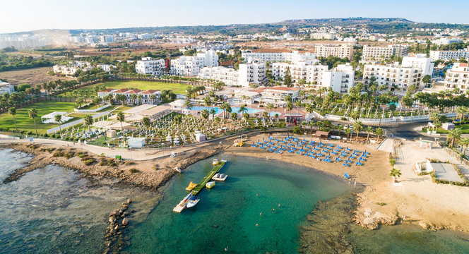Aerial bird's eye view Pernera beach Protaras, Paralimni, Famagusta, Cyprus. The tourist attraction golden sand bay with sunbeds, water sports, hotels, restaurants, people swimming in sea from above.