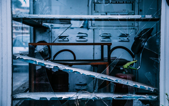 Machinery And Fire Extinguisher In Abandoned Factory Seen Through Broken Glass