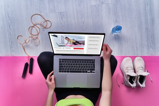 Fitness woman watches sports online workouts at home on computer