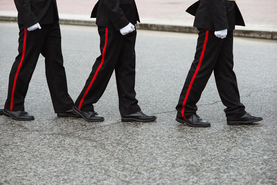 Three Russian cadets in a ceremonial black uniform go one after another. Crop by waist. People in uniform
