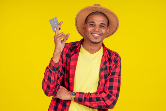 afro brazilian man with credit card in stusio on yellow background.farmer taking a loan in a bank for small business in agriculture