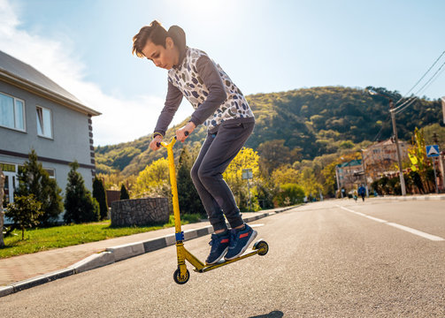 A teenage boy performs a trick on a scooter, Bouncing up on it. In the background, an empty street and a view of the mountain. Side view. Concept of extreme sports, tricks and youth activity