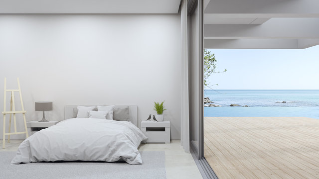 Bed on beige marble floor of bright bedroom against empty white wall in modern beach house or luxury pool villa. Minimal home interior 3d rendering with sea view.