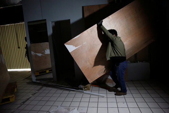 A worker moves a wood plank inside a clothing store after it went out of business following the coronavirus disease (COVID-19) outbreak, in Beijing