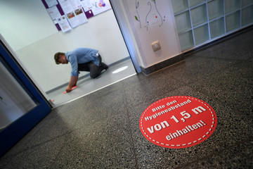 Sebastian Ruppert of Repro Ruppert from Unterhaching delivers stickers that remind pupils to keep the necessary distance at a vocational school for pharmacy technicians