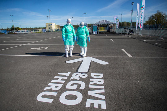 Medical workers stand next to the drive-through mobile testing side for the coronavirus disease (COVID-19) in Bydgoszcz