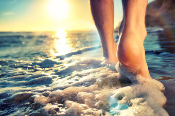Closeup of a man's bare feet walking at a beach at sunset touching the water, with the sun and nice lens flare
