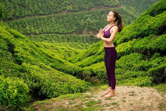 woman in violet cloth doing yoga on tea plantations in Munnar hill Kerala India