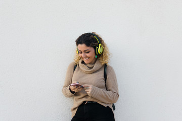 Young happy woman in beige casual sweater smiling while using headphones and mobile phone with white wall on background