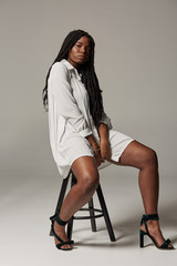 Sensual plus size African American lady with braids in trendy white dress sitting on stool and looking at camera against gray background