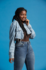 Positive beautiful African American woman with braids in denim outfit smiling and looking at camera against blue background