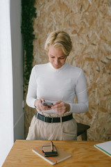 Focused adult businesswoman looking at camera while using mobile phone near notepad on wooden table in light office