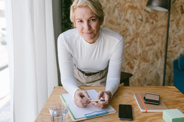 Focused adult businesswoman looking at camera while taking notes of plan on clipboard bending on wooden table in light office Wall mural