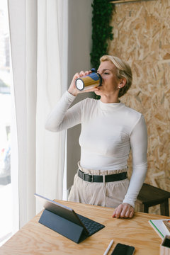 Dreamy stylish blond woman at wooden table with tablet and stationery taking sip of coffee from disposable cup looking away in office