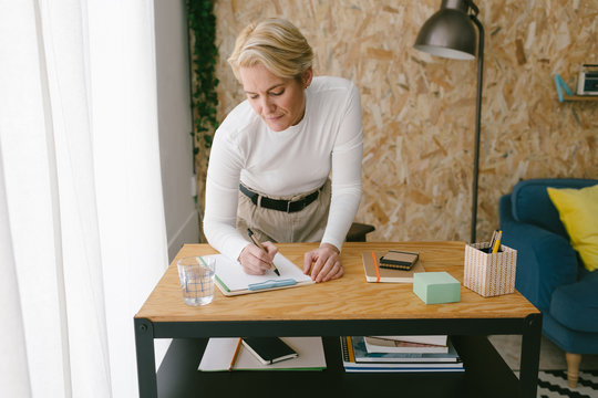 Focused adult businesswoman taking notes of plan on clipboard bending on wooden table in light office