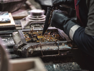 Side view from above of crop unrecognizable craftsman in black gloves using metal tools while pouring material in metal stencil in factory