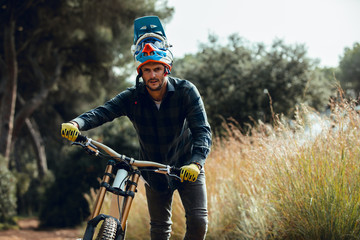Handsome man in helmet walking looking at camera while carrying mountain biking bike after practice in meadow