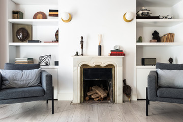 Comfortable grey seats located near fireplace and bookshelf in cozy living room in stylish apartment Fotomurales