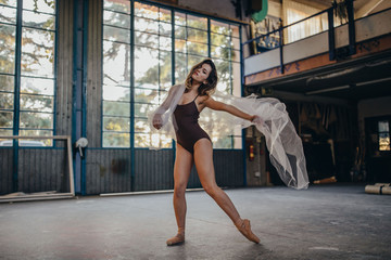 Full body of slim graceful female dancer looking at camera in black bodysuit and pointe shoes performing dance with transparent light tulle during rehearsal in studio