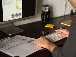 Detail of man's hands working at home desk with computer over the Internet reviewing statistics and invoice