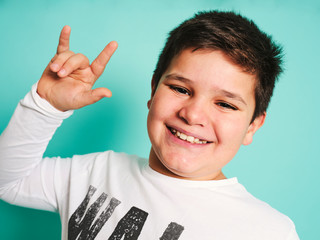 Joyful confident chubby plus size preteen boy in casual clothes looking at camera and laughing while making rock and roll sign against turquoise background