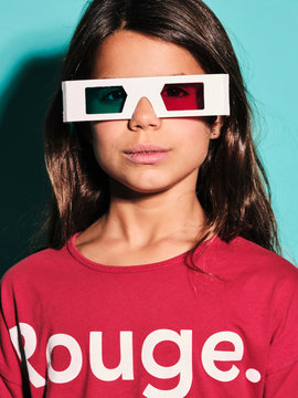 Portrait of happy preteen girl in white plastic stereoscopic glasses with red and blue lens smiling at camera while watching 3d graphic film with pleasure against turquoise background in modern studio
