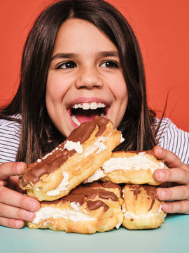 Closeup of cheerful little girl in casual wear enjoying sweet eclairs with chocolate while sitting at table against red background