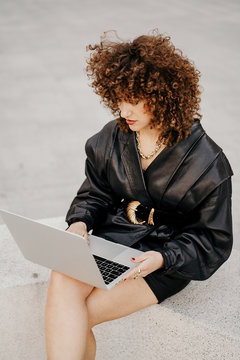 From above businesswoman in black leather outfit sitting on border and browsing data on laptop while working on remote project on city street