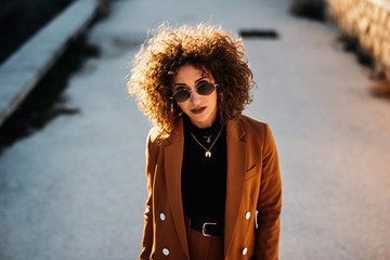 Stylish young female model in trendy outfit and sunglasses standing in pose and looking at camera with empty city street on blurred background