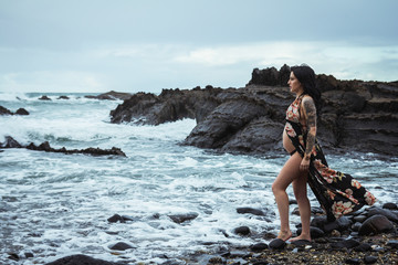 Side view of sensual pregnant woman looking away wearing long waving lingerie robe walking with bare belly on rocky coast in gloomy day