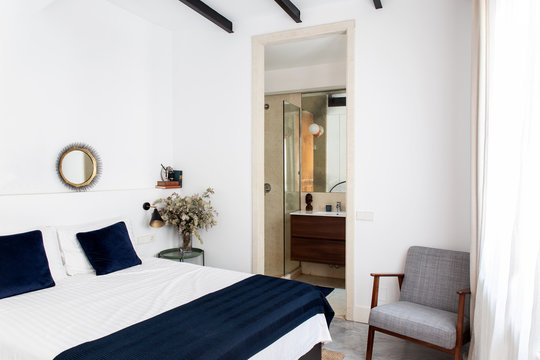 Comfortable bed with white and blue duvet and soft armchair located near bathroom doorway in cozy bedroom of modern apartment